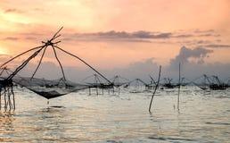 Schattenbild der traditionellen Fangtechnik unter Verwendung eines quadratischen BambusKeschers mit Sonnenaufganghimmelhintergrun Lizenzfreies Stockbild