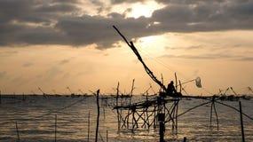 Schattenbild der traditionellen Fangtechnik unter Verwendung eines quadratischen BambusKeschers mit Sonnenaufganghimmelhintergrun Stockbild