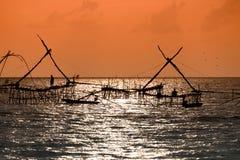Schattenbild der traditionellen Fangtechnik unter Verwendung eines quadratischen BambusKeschers mit Sonnenaufganghimmelhintergrun Stockbilder