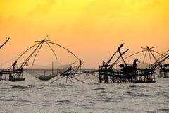 Schattenbild der traditionellen Fangtechnik unter Verwendung eines quadratischen BambusKeschers mit Sonnenaufganghimmelhintergrun Stockfotografie