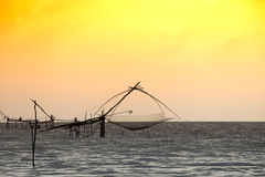 Schattenbild der traditionellen Fangtechnik unter Verwendung eines quadratischen BambusKeschers mit Sonnenaufganghimmelhintergrun Lizenzfreies Stockfoto
