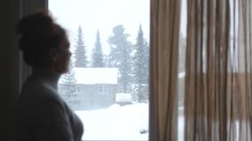 Schattenbild der unscharfen reifen Frau im gealterten Aufpassen in Fenster auf schönen schneebedeckten Bergen Stockbilder