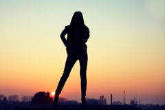 Schattenbild der verlockenden Frau auf Dachspitze bei städtischem Sonnenuntergang Stockfotografie