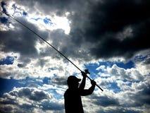 Schattenbild der werfenden Angelrute des Fischers im See Lizenzfreie Stockbilder