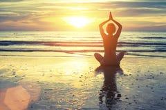 Schattenbild der Yogafrau meditierend auf dem Ozeanstrand Eignung lizenzfreie stockbilder