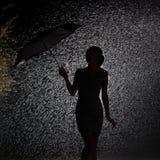 Schattenbild der Zahl eines jungen Mädchens im Regen, glückliche junge Frau, die einen Regenschirm hält, der weg durchbrennt lizenzfreies stockfoto