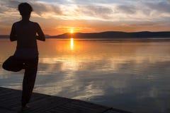 Schattenbild des übenden Yoga und des Meditierens der Frau auf dem See a Stockfotografie