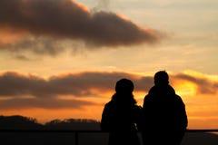 Schattenbild des überwachenden Sonnenuntergangs der Paare Stockfotos