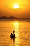 Schattenbild des afrikanischen Fischers im Kanu am Sonnenuntergang Stockfotografie
