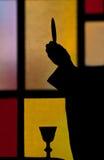 Schattenbild des anhebenden Hauptrechners des Priesters Lizenzfreies Stockbild