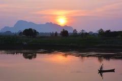Schattenbild des asiatischen Fischers schwimmend in das Boot bei dem Sonnenuntergang Stockbilder