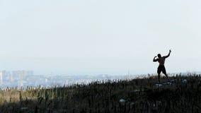 Schattenbild des athletischen Mannes des Afroamerikaners mit dem nackten Torso, der auf dem Felsen aufwirft lizenzfreies stockbild