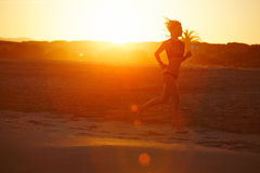 Schattenbild des athletischen weiblichen Läufers, der entlang den Strand einen erstaunlichen orange Sonnenuntergang auf Hintergru Stockfotografie