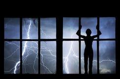 Schattenbild des aufpassenden Blitzes, des Donners, des Regens und des Sturms des Mannes Lizenzfreies Stockfoto