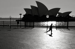 Schattenbild des australischen Mannes läuft nahe dem Opernhaus Stockfotografie