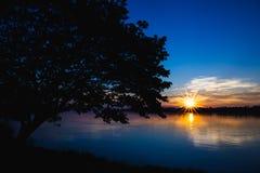 Schattenbild des Baums auf links mit Fluss und Sonne erweitern sich auf Sonnenuntergang Lizenzfreie Stockfotos