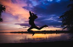 Schattenbild des Baums dazu und Männer springen mit schönen Farbsonnen Stockbild