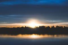 Schattenbild des Baums mit Fluss und des Sonnenuntergangs mit sunflare Stockfoto
