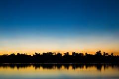 Schattenbild des Baums und des Flusses mit schöner Farbe auf Sonnenuntergang Stockfotografie