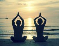 Schattenbild des übenden Yoga der jungen Paare auf Seestrand während des Sonnenuntergangs Stockfotografie