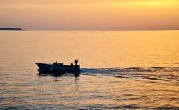 Schattenbild des Bootes bei Sonnenuntergang im Meer Lizenzfreies Stockbild