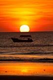 Schattenbild des Bootes im Ozean während des Sonnenuntergangs Stockbild