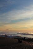 Schattenbild des bunten Sonnenuntergangs der Leute auf atlantischer Küste mit brechenden Wellen mit Gebirgsla rhune, capbreton, F Stockbild