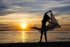 Schattenbild des dünnen Frauentanzens mit Schal auf dem Strand Stockfotos