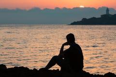 Schattenbild des denkenden Mannes im Sonnenaufgang Lizenzfreie Stockfotografie