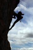 Schattenbild des Felsenbergsteigers eine Klippe steigend Stockfotografie