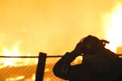 Schattenbild des Feuerwehrmanns an einer Flamme Stockfoto