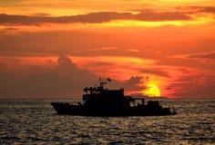 Schattenbild des Fischerbootes im Meer mit dem Sonnenhintergrund Stockfotos