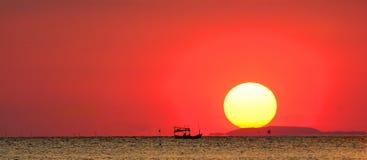 Schattenbild des Fischerbootes im Meer mit dem Sonnenunterganghintergrund Stockbild