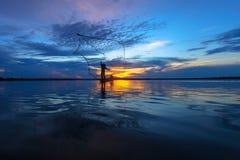 Schattenbild des Fischers im hölzernen Boot Lizenzfreies Stockfoto