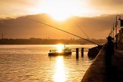 Schattenbild des Fischers mit dem Wunsch der Stange auf der Bank von Neva-Fluss Stockfoto