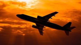 Schattenbild des Fliegenflugzeugs auf Sonnenunterganghintergrund Lizenzfreies Stockbild