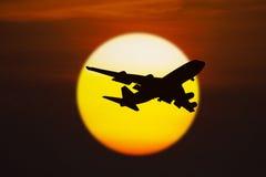 Schattenbild des Flugzeuges auf Sonnenuntergang Lizenzfreie Stockfotos