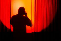 Schattenbild des Fotografen auf dem orange courtain, das Fotos macht Lizenzfreie Stockfotos