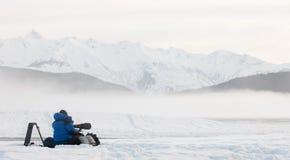 Schattenbild des Fotografen auf dem Schnee mit Stativ und Kamera Lizenzfreie Stockbilder