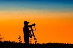 Schattenbild des Fotografen Foto der Landschaft während SUs machend Stockfoto