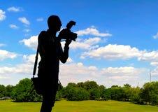 Schattenbild des Fotografen mit Kamera vor dem hintergrund des Grüns befestigte Rasen Stockfotografie