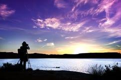Schattenbild des Fotografen mit seiner Ausrüstung während des Sonnenuntergangs stockbilder