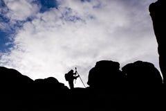Schattenbild des Fotografen mit Stativ gegen den Himmel stockfotografie