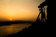 Schattenbild des Fotografwartesonnenuntergangs am Flussufer mit Lizenzfreie Stockfotos