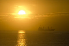 Schattenbild des Frachtschiffs über dem Sonnenaufgang Stockfotos