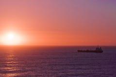 Schattenbild des Frachtschiffs über dem Sonnenaufgang Lizenzfreie Stockfotografie