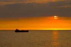 Schattenbild des Frachtschiffs über dem Sonnenaufgang Stockfotografie