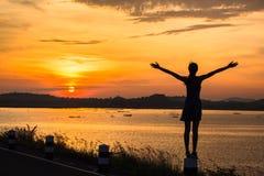 Schattenbild des Frauengefühls frei und des Sonnenaufgangs stockfotografie