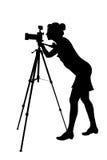 Schattenbild des Frauphotographen und des Stativs Stockfoto