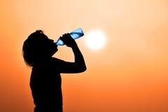 Schattenbild des Gefühls des Trinkwassers der jungen Frau (durstiges, heißes ein Bedarf, Wasser zu trinken) Stockfotografie